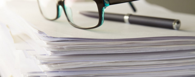 stacks of paperwork with glasses on them