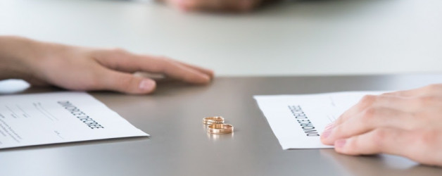 Divorce paperwork and wedding rings sit on a table; clarity about custody arrangements and property can expedite a divorce